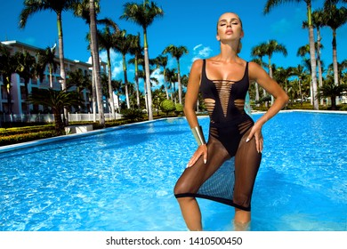 Elegant sexy woman in the bikini on the sun-tanned slim and shapely body is posing near the swimming pool - Image