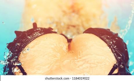 Elegant sexy woman in bikini with tanned slim body posing near the swimming pool. Close-up detail of beautiful woman body with big breast wearing black bikini on hotel resort Beach. Sexy boobs in pool