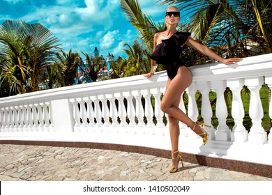 Elegant sexy woman in the black bikini on the sun-tanned slim and shapely body is posing near the swimming pool and palm trees - Image