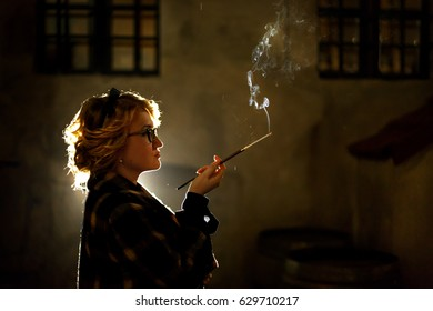 Elegant sexy woman holding cigarette and smoking outdoors, face close-up, portrait of mysterious woman in vintage coat, french noire atmosphere, detective concept