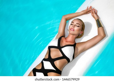 Elegant sexy woman in luxury bikini on the sun-tanned slim and shapely body is posing near the swimming pool. Sunbathing By Swimming Pool On Travel . Beauty, Wellness, Lifestyle - Image