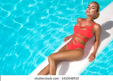 Elegant sexy woman in the orange bikini on the sun-tanned slim and shapely body is posing near the swimming pool - Image