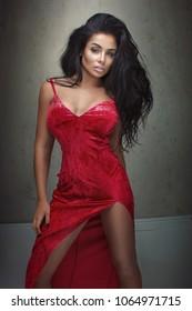 Elegant sexy woman posing in red maxi dress.