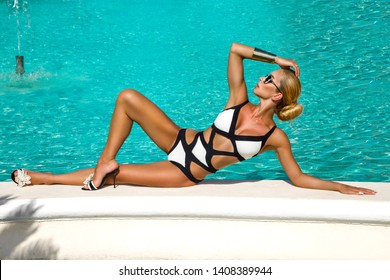 Elegant sexy woman in the white bikini on the sun-tanned slim and shapely body is posing near the swimming pool - Image
