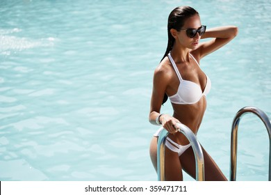 Elegant sexy woman in the white bikini on the sun-tanned slim and shapely body is posing near the swimming pool