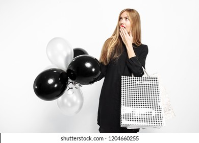 Elegant shocked girl, in black dress, with shopping bags and black balls in her hands isolated on white background . Black Friday, shopping, discounts