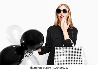 Elegant shocked girl, in black dress with sunglasses, with bags and black balls in her hands isolated on white background . Black Friday, shopping, discounts