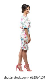 Elegant shy feminine fashion female model in floral dress smiling and looking down. Side view. Full body length portrait isolated on white background.