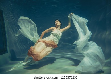 elegant slender girl swims underwater like a free diver in a white evening dress with beautiful fabric