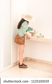 Elegant slim Caucasian or Asian girl with dark long hair, white hat, leather bag and Tiffany blue clothes fills reusable water bottle with drinking water in a bathroom. Ecology concepts.