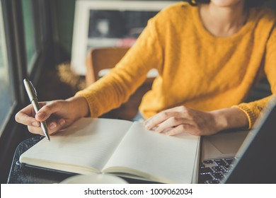 Elegant smart woman in yellow dress sitting at table in cafe and writing notebook. On table is laptop, smartphone and cup of coffee. Freelancer working in coffee shop. Student learning online.
