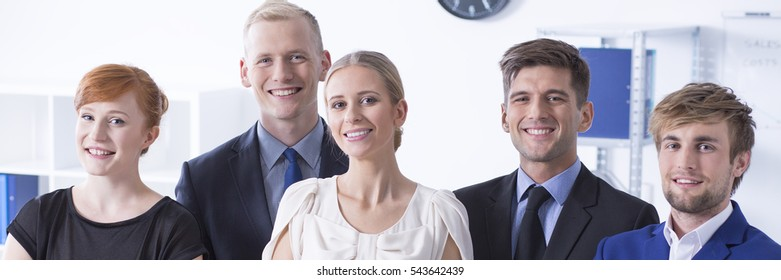 Elegant smiling young executive staff in office