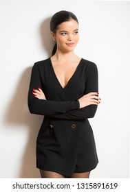 Elegant smiling young woman in black dress.