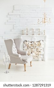 Elegant soft arm-chair near a fireplace. Luxury interior in white colors. Armchair with fabric upholstery