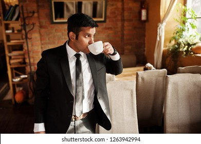Elegant south asian indian business man in black suit posed indoor cafe and drinking tea.