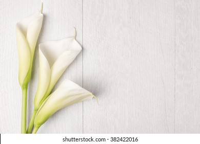 Elegante Frühlingsblume, Calla Lilie auf rustikalem Holztisch. Zum Hochzeitshintergrund. Draufsicht mit Kopienraum