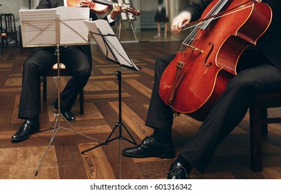 Elegant string quartet performing at wedding reception in restaurant, handsome man in suits playing violin and cello at theatre play orchestra close-up, music concept