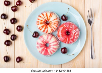 Elegant striped sponge cakes with a shiny glaze, coconut flakes and sugar pearls in the shape of a doughnut and sweet cherries on wooden table