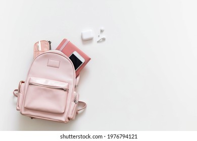 Elegant student female backpack full of schooler supplies isolated on white with copy space. Top view personal college bag storage with accessories and electronic devices. Back to school concept