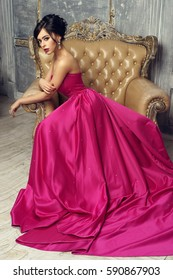 Elegant stunning woman sitting in armchair and looking at you. Pretty lady with hairstyle wearing pink ball gown or evening dress.