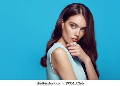 Elegant styling young woman with hairstyle and makeup. Caucasian female model wear jewellery over a blue background.