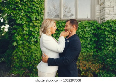 elegant and stylish bride with light curly hair dressed in a white dress, a white jacket and white dress standing in a summer garden on the background of old big houses along with her elegant man