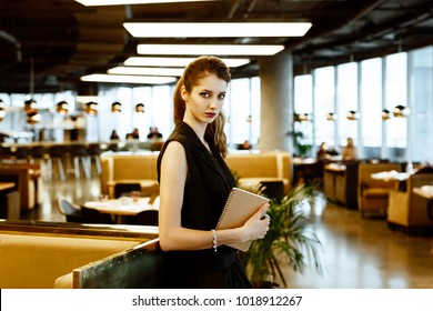 The elegant stylish business woman in a black suit welcomes guests in the restaurant hall with a notebook in hands. hostess