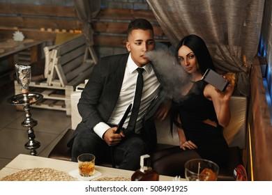 Elegant stylish couple smoking hookah and makes selfie on smartphone