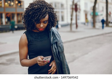 elegant and stylish dark-skinned girl with curly hair walking around the summer city