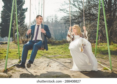elegant stylish groom and beautiful blonde bride on swings on the background of a park