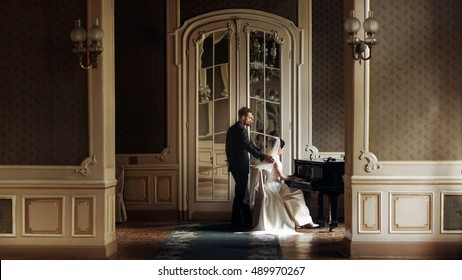 elegant stylish handsome groom looking at his gorgeous bride playing the piano. reflection in the mirror. unusual luxury wedding couple in retro style