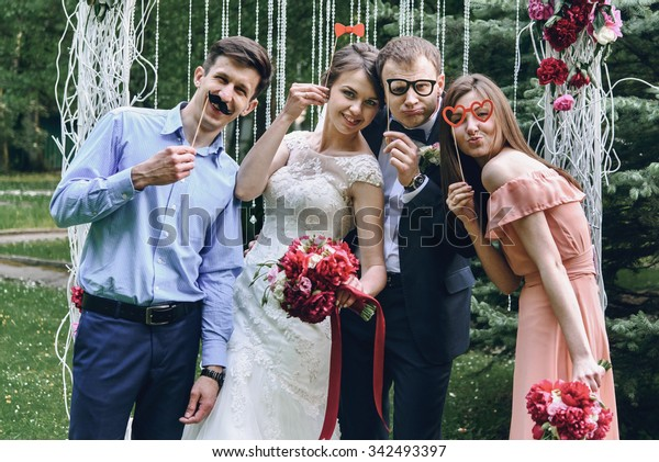 elegant stylish happy guests and bride and groom having funny photos on the background of arch, photo booth