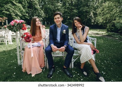 elegant stylish happy guests and bridesmaid waiting for a wedding ceremony  on the background of park