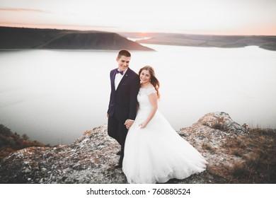 Elegant stylish happy wedding couple, bride, gorgeous groom on the background of sea and sky