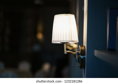 Elegant, stylish and simple lamp sconces on the wall in the room. Interior details, lighting in the interior. Close-up and beautiful bokeh.