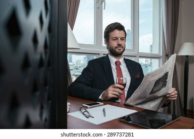 Elegant successful businessman drinking wine and reading fresh newspaper