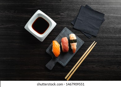 Elegant sushi on wood table. Some Nigiri, with soy sauce and chopstick