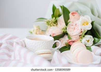 Elegant sweet dessert macarons, cup of coffee and pastel colored beige flowers bouquet