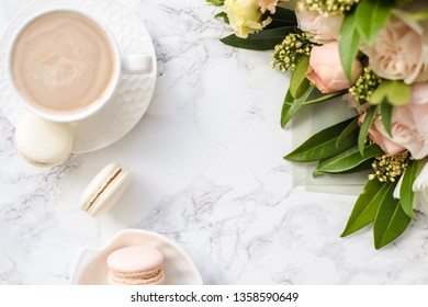 Elegant sweet dessert macarons, cup of coffee and pastel colored beige flowers bouquet on white marble