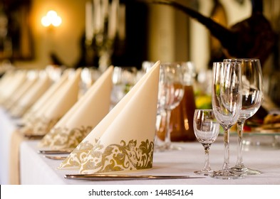 Elegant table set for a catered function with a low angle shallow depth of field view of the linen and glassware