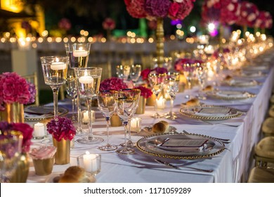 Elegant table set with glasses decorated in gold, lighted candles and red flowers