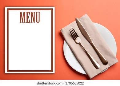 Elegant table setting and empty menu on orange background, flat lay. Space for text