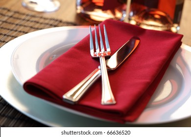 Elegant table setting with fork, knife and red napkin
