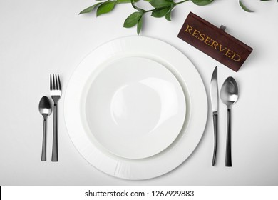 Elegant table setting with RESERVED sign on white background, top view