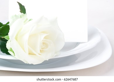 Elegant tableware with rose and invitation.