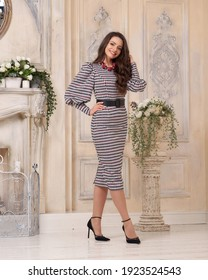 Elegant tall slim beautiful caucasian woman with long brunette hair and natural make-up wearing white and black squared dress standing and posing in bright beige room interior