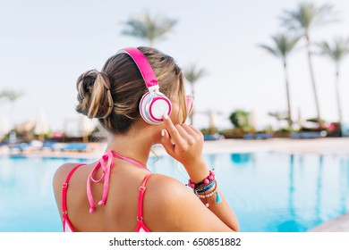 Elegant tanned girl with cute hairstyle standing in front of big outdoor pool ready to swim in sunny morning. Portrait of young woman in pink headphones and trendy bracelets resting on resort