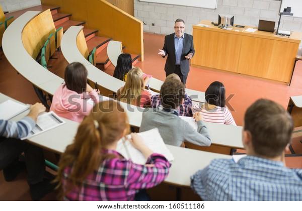 Elegante insegnante con studenti seduti presso la sala conferenze del college