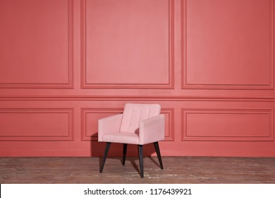 Elegant textured soft pink armchair stands on the old parquet on the coral wall background in the studio. It drops shadow. Horizontal.