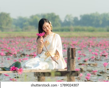 An elegant Thai woman wearing traditional Thai clothes adorned with gold ornaments carrying lotus flowers collected from a lotus field